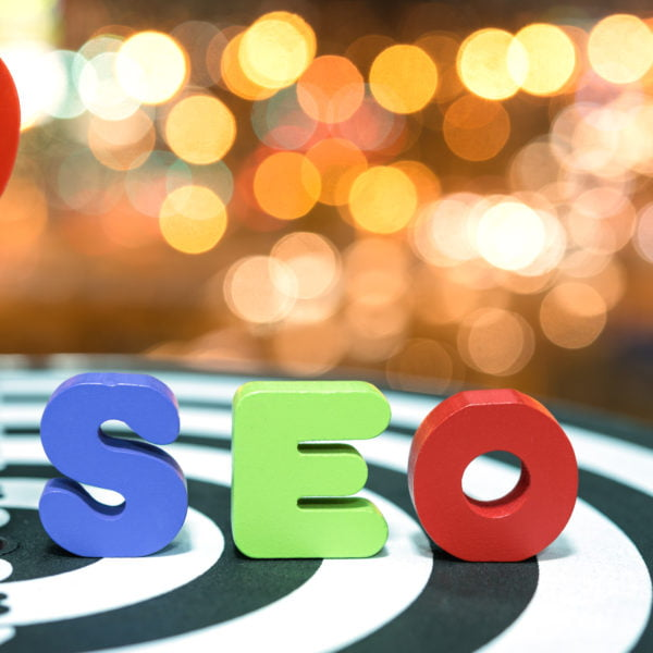 Search Engine Optimization target marketing concept with red dart target hitting in bullseye on dartboard and colorful alphabet wood letters SEO over light blurred bokeh background